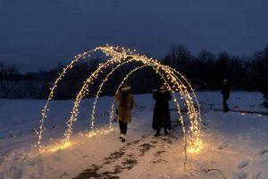 Winter Walk - Attendees Walk Under Lit Archway